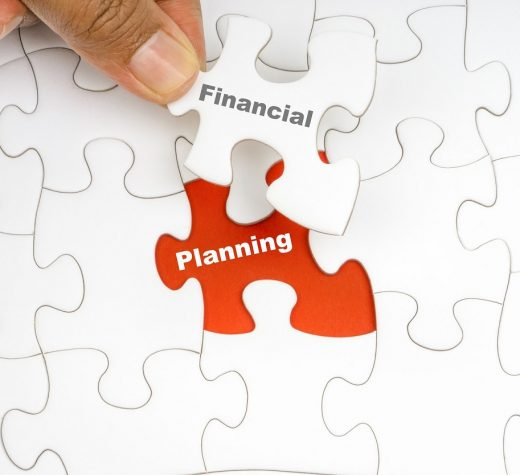 Hand holding piece of jigsaw puzzle with word FINANCIAL PLANNING. Selective focus