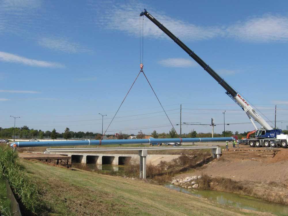 Crane lifting a pipe