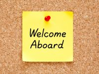 Welcome Aboard written on an yellow sticky note pinned on a cork bulletin board.