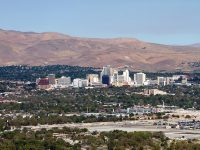 The city skyline of Reno, Nevada with the surrounding urban area and foothills in the distance.